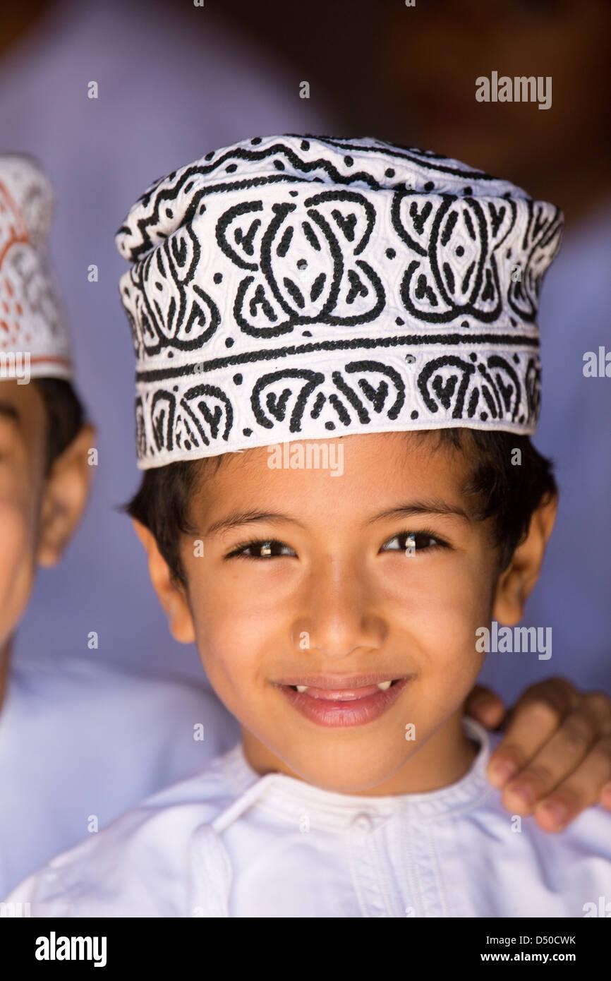 Eine omanische Schuljunge in eine weiße Schale Strich eine traditionelle Mütze oder Kopfschmuck tragen Stockbild