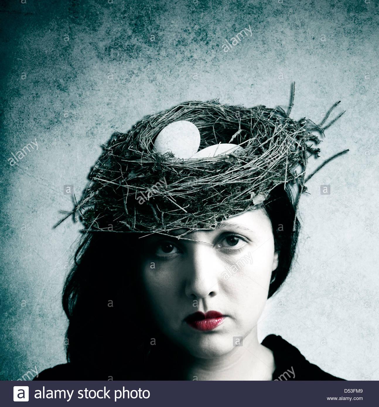 Frau trägt Vogelnest als Hut Stockbild