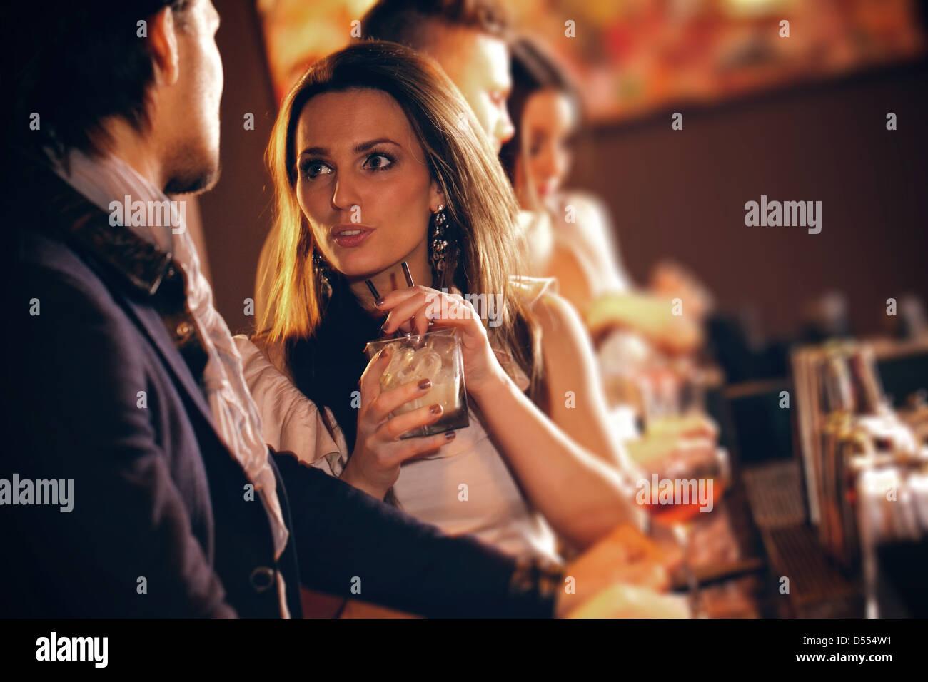 Junge Frau mit einem Glas Wein im Gespräch mit einem Mann an der bar Stockbild