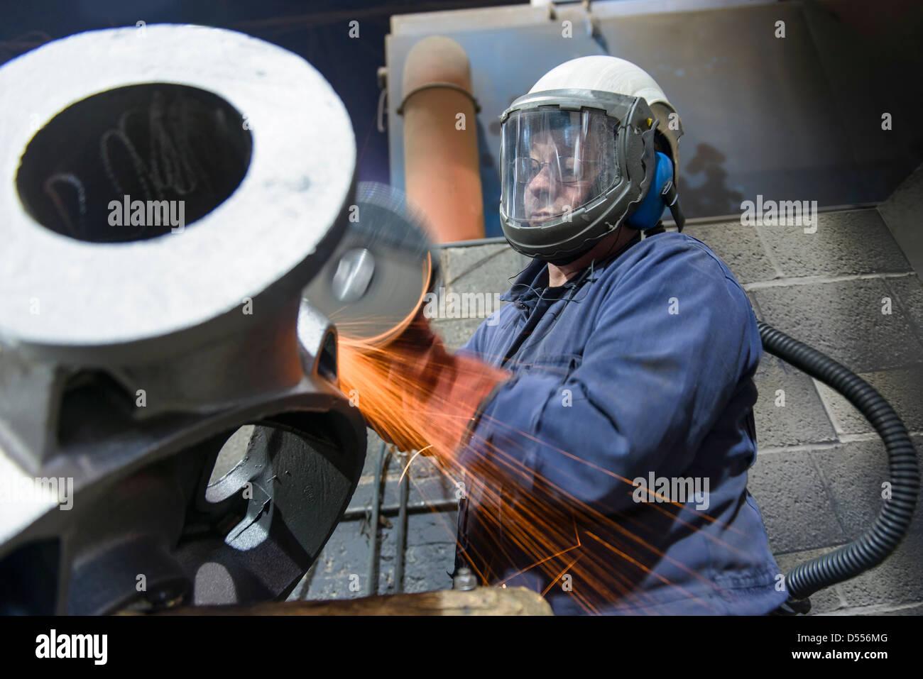 Arbeiter Schleifen Gehäuse in Metall Gießerei Stockbild