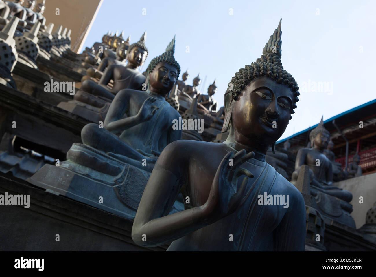 Eine Wiederholung der Buddha-Statuen im Gangaramaya Tempel in Colombo, Sri Lanka Stockbild