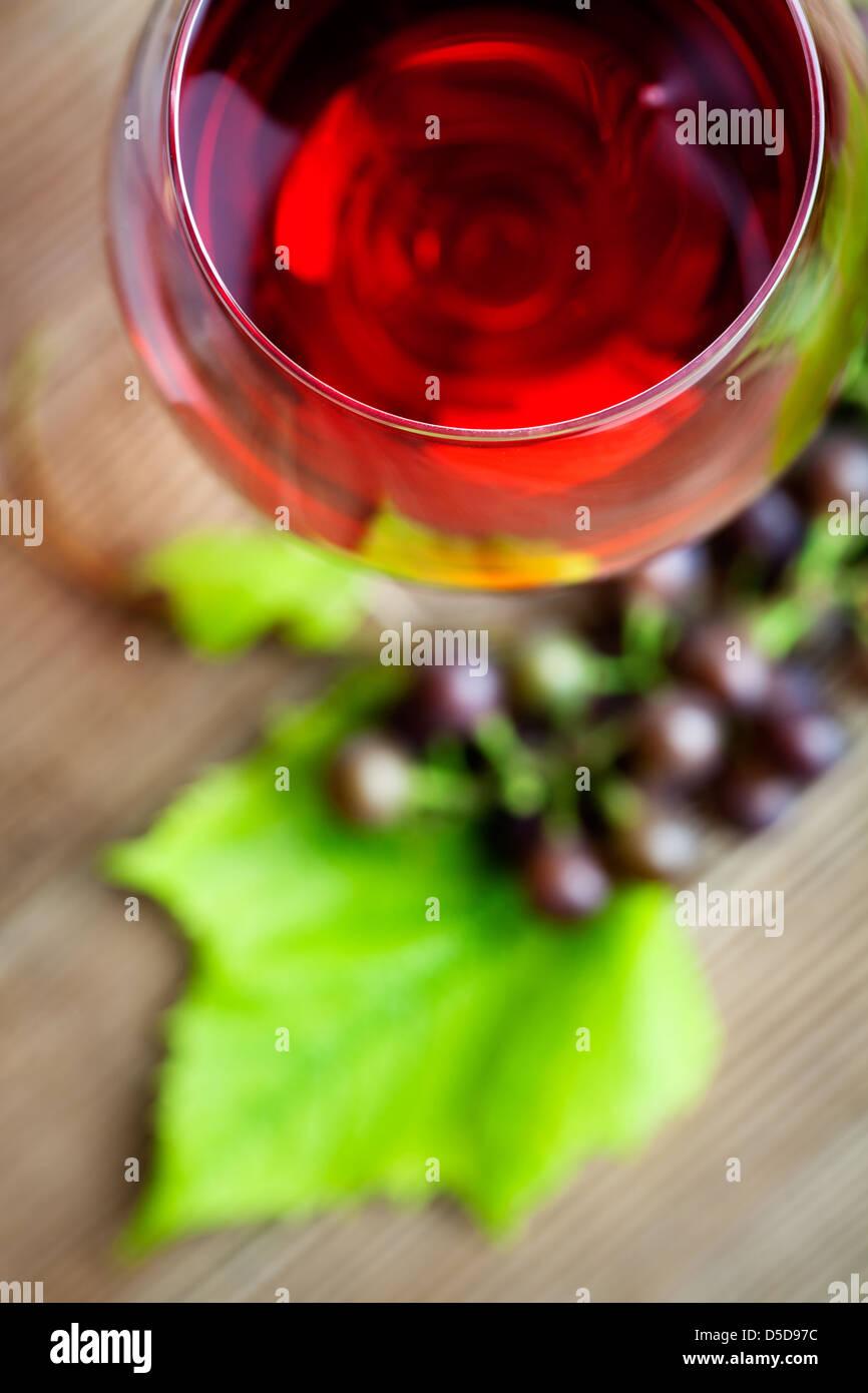 Glas Rotwein mit Trauben auf Tisch Stockbild