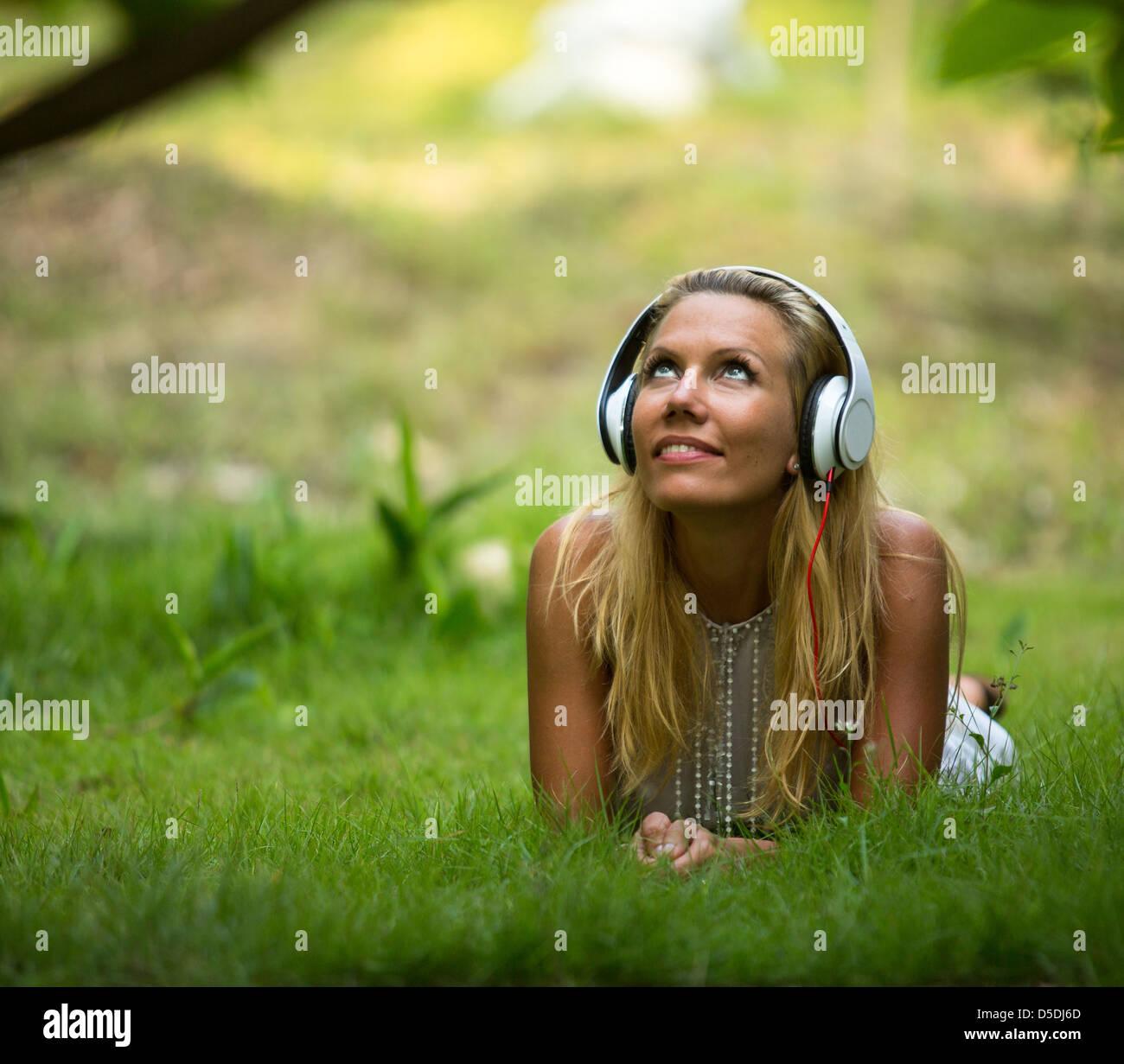 Glück-Mädchen mit Kopfhörern genießen Natur und Musik am sonnigen Tag Stockbild