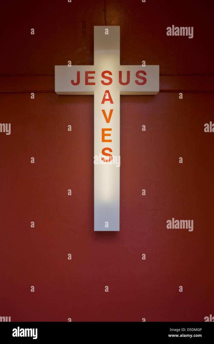 Ein Jesus rettet Neon-Schild am Eingang einer evangelischen Kirche in Peckham, Südlondon. In der Nähe sind die Stimmen Stockfoto