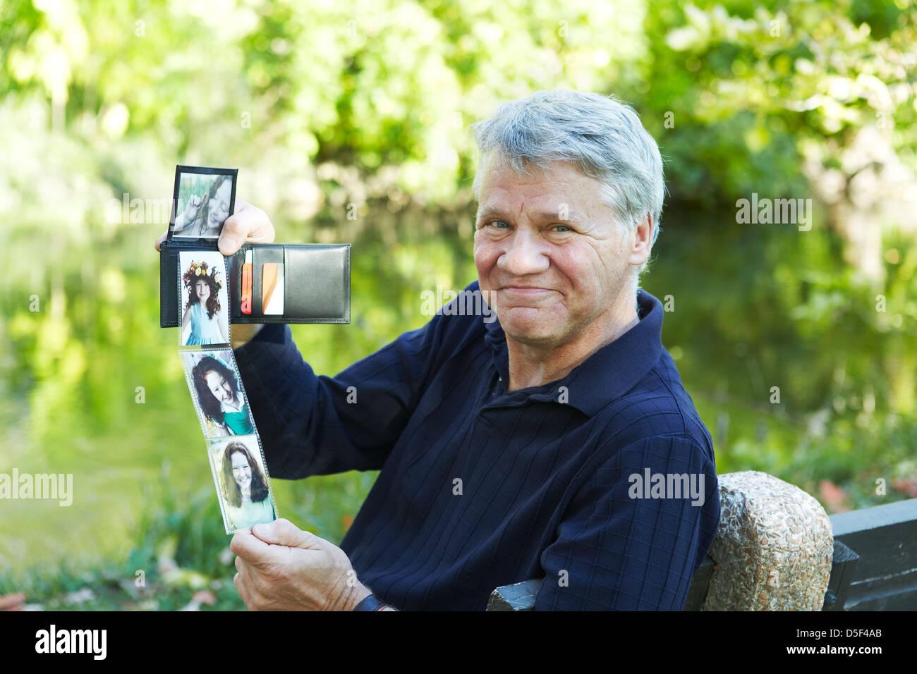 Großvater zeigt Fotos von seiner Enkelin Stockbild