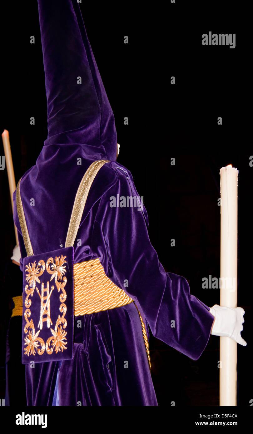 Büßer mit Kerzen in der Abenddämmerung in der Semana Santa-Prozession in Málaga, Andalusien, Spanien Stockfoto
