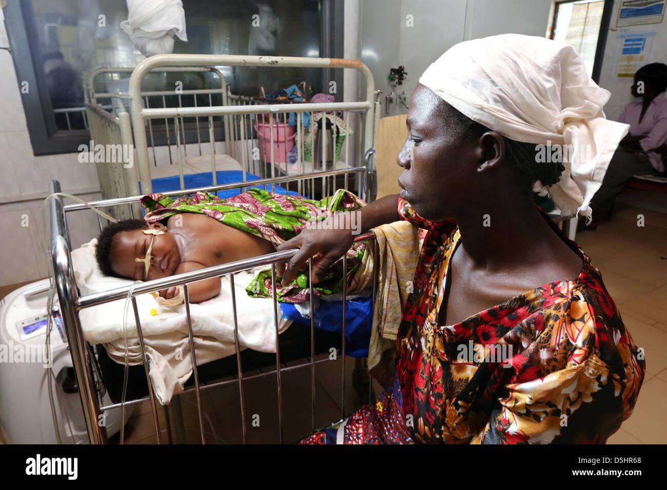 Mutter schaut ihr krankes Baby in einem Krankenhaus in Techiman, Ghana Stockbild
