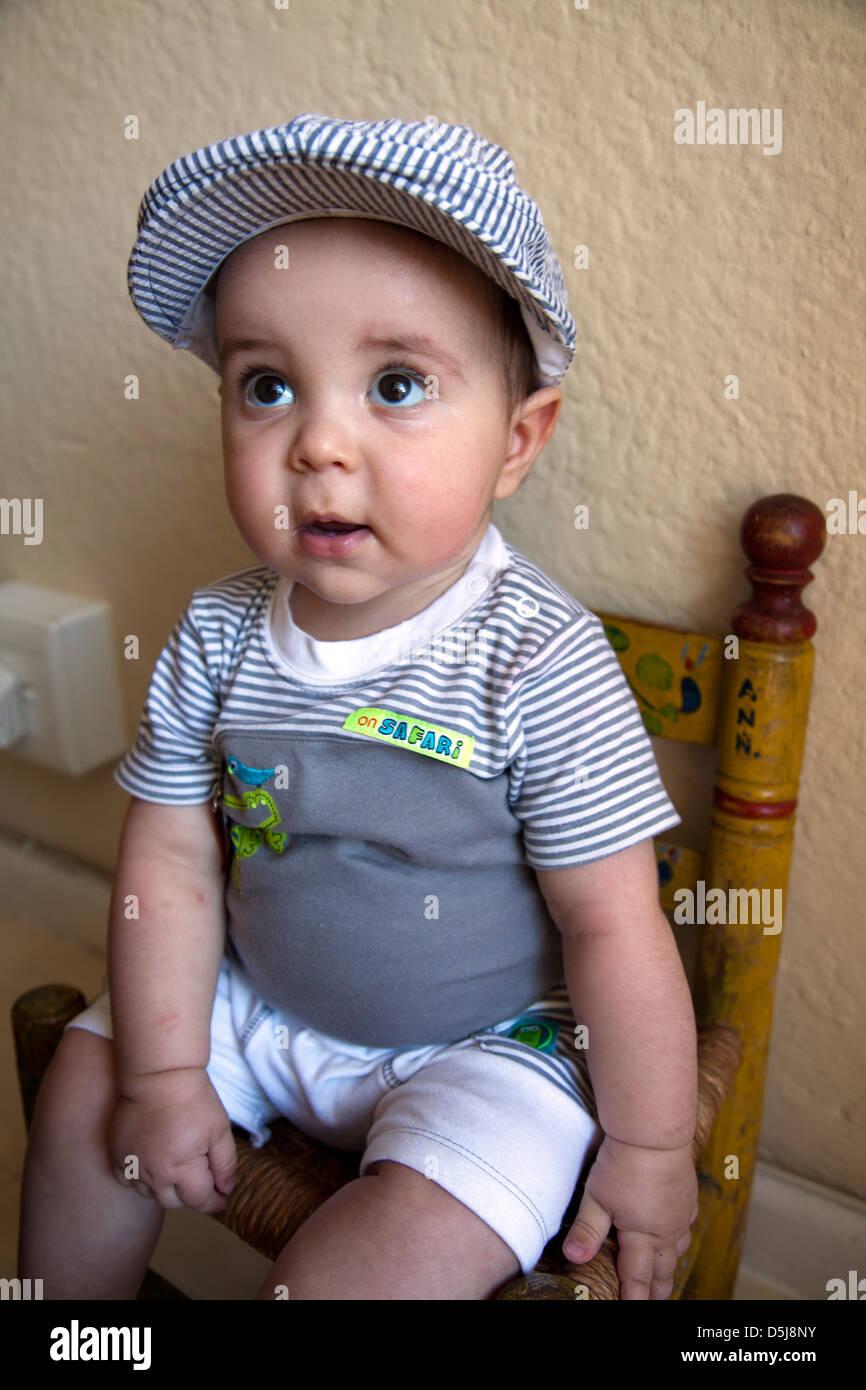 Baby Boy Portrait tragen Mütze und sitzen auf Stuhl Stockfoto