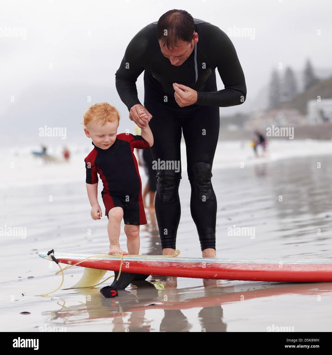 Vater und Sohn (2-3) am Strand von Surfbrett Stockbild