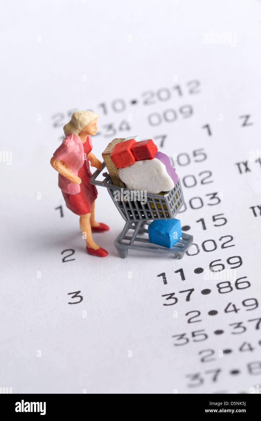 Miniatur-Figur einer Frau mit einem Warenkorb auf einem Bon - shopping Konzept Stockbild