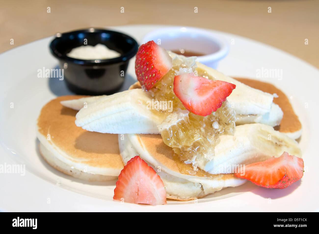 Pfannkuchen mit Bananen Erdbeeren Honeycomb Ahornsirup und Butter Closeup Stockbild