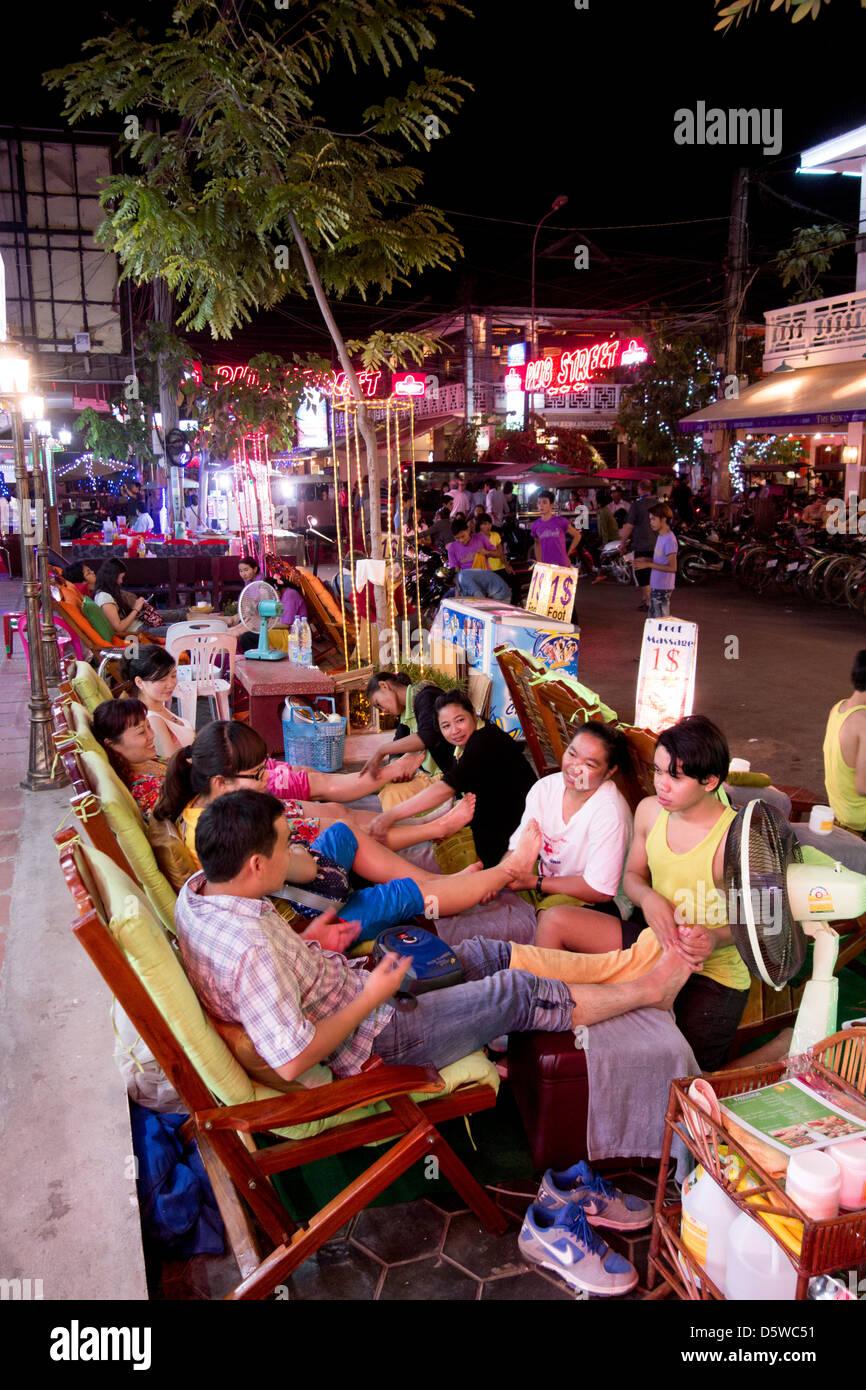 Masseure und Masseurinnen massieren Touristen auf der Straße in der Nacht im Pub Street Ausgehviertel Siem Stockbild