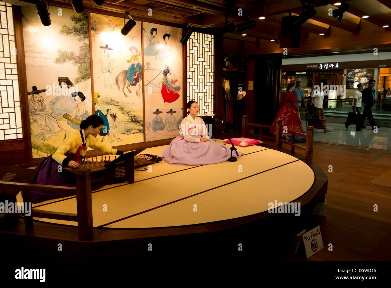 Koreanische Frauen spielen traditionelle Musik und Gesang in der Abflug-Lounge von Incheon Flughafen Seoul Südkorea, Stockbild