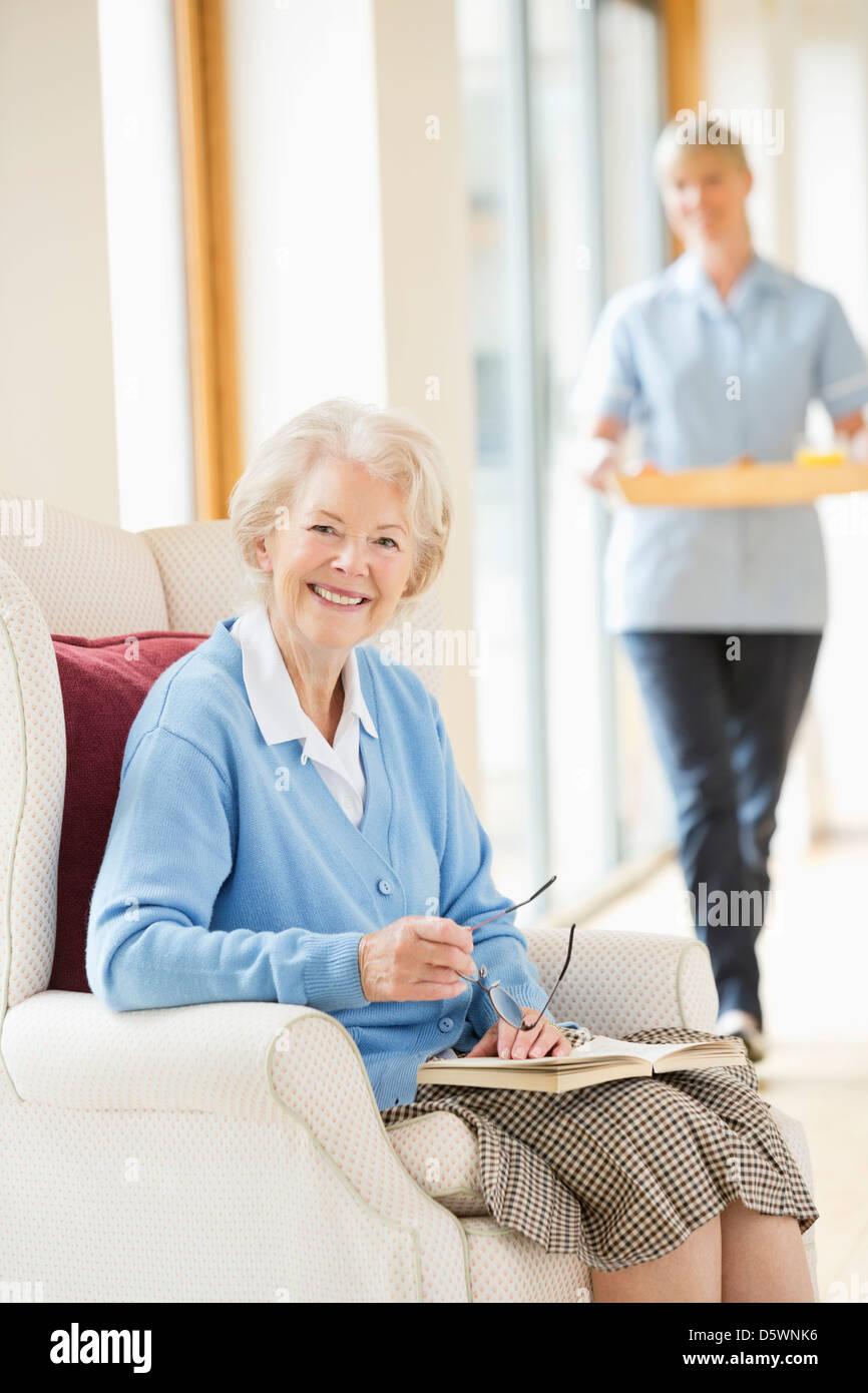 Ältere Frau lächelnd in Sessel Stockbild
