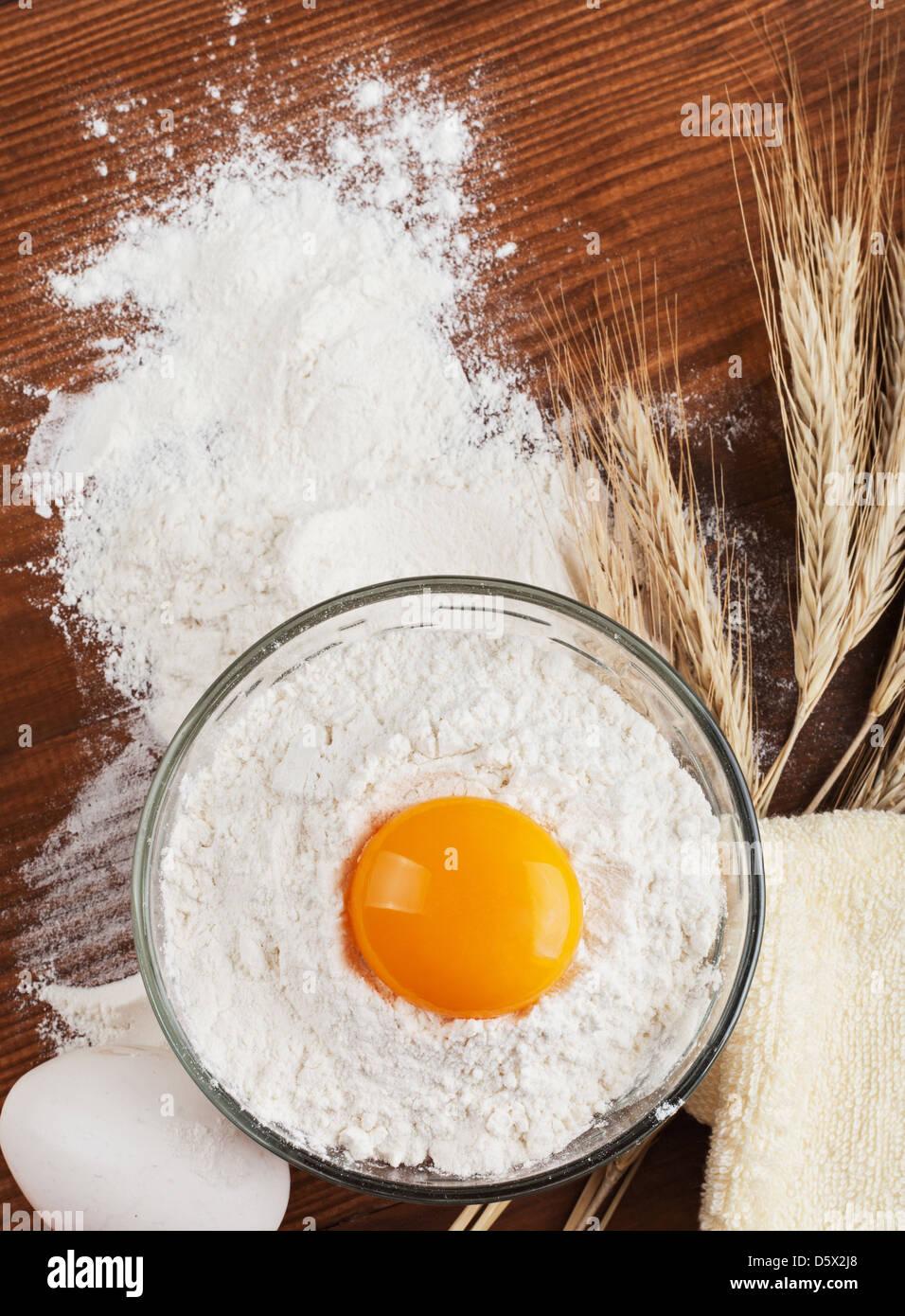Bereiten Sie die Zutaten für das Backen. Mehl, Ei auf einem Holztisch. Ährchen Weizen Stockbild