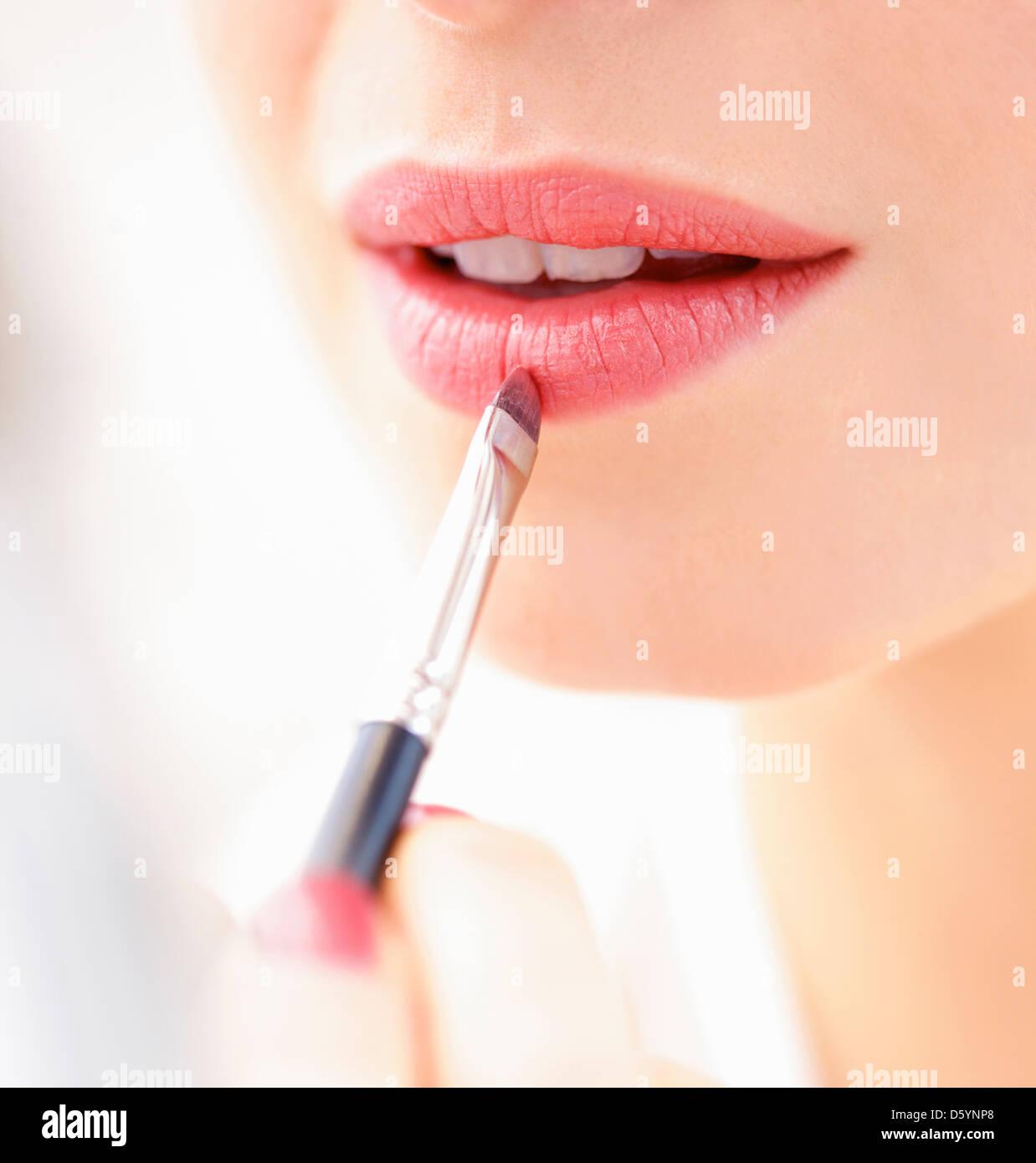 Frau Auftragen von Lippenstift mit Make-up Pinsel, Nahaufnahme Stockfoto