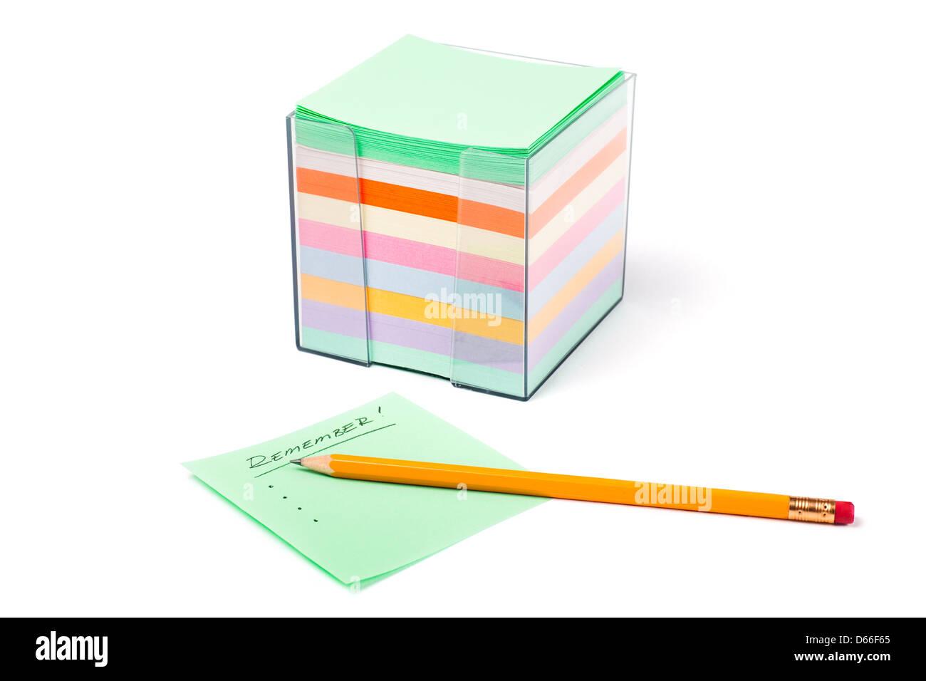 Behälter mit Notizpapier in verschiedenen Farben auf weißem Hintergrund. Das Wort nicht vergessen! wird Stockbild