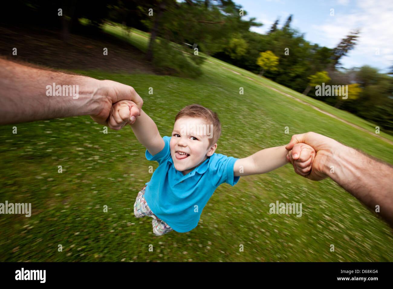 Vater Spinning Sohn draußen im Park Stockbild