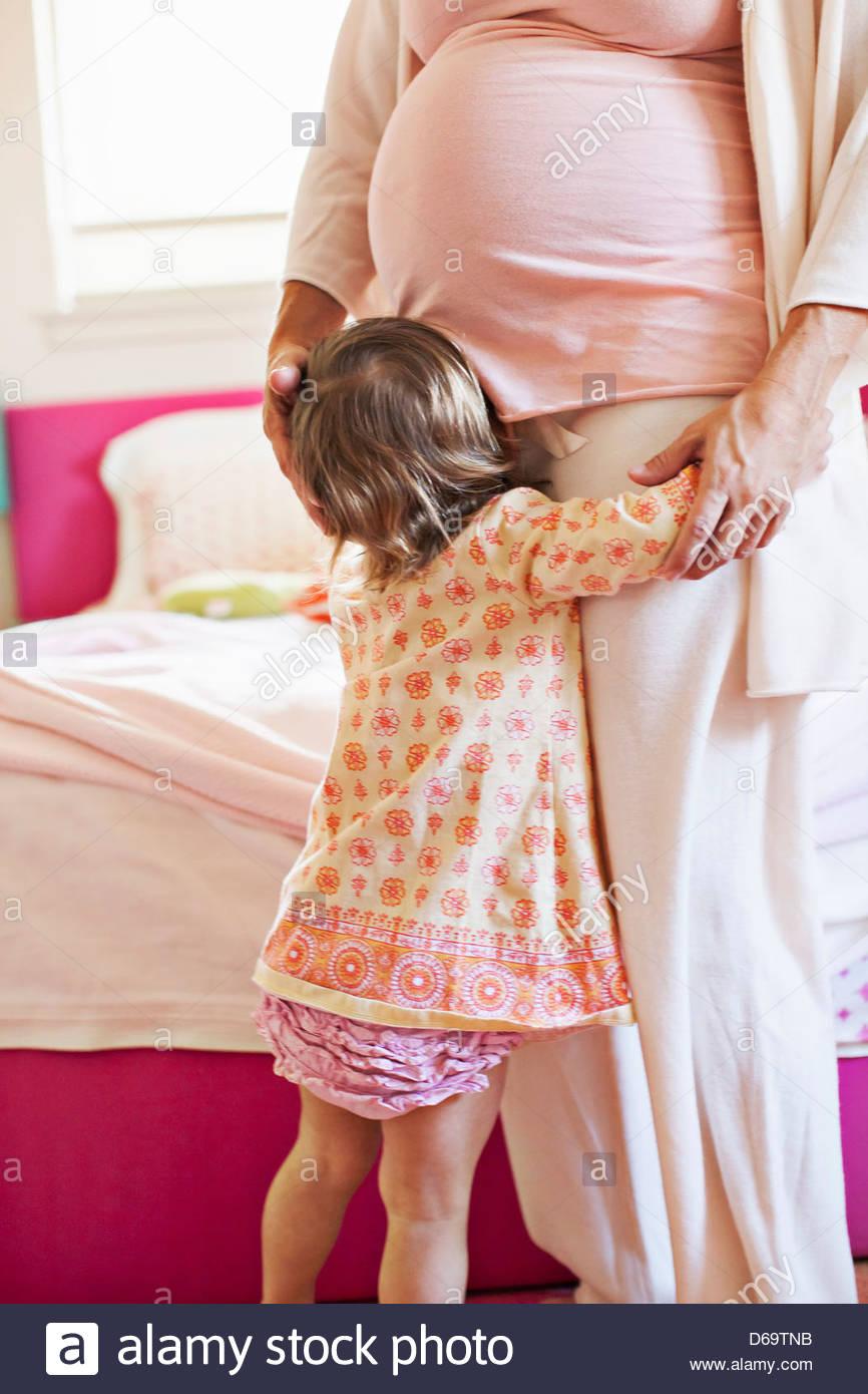 Kleinkind Mädchen umarmt schwangere Mutter Stockbild