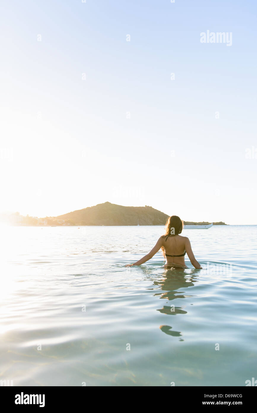 Frau zu Fuß im Wasser am Strand Stockbild