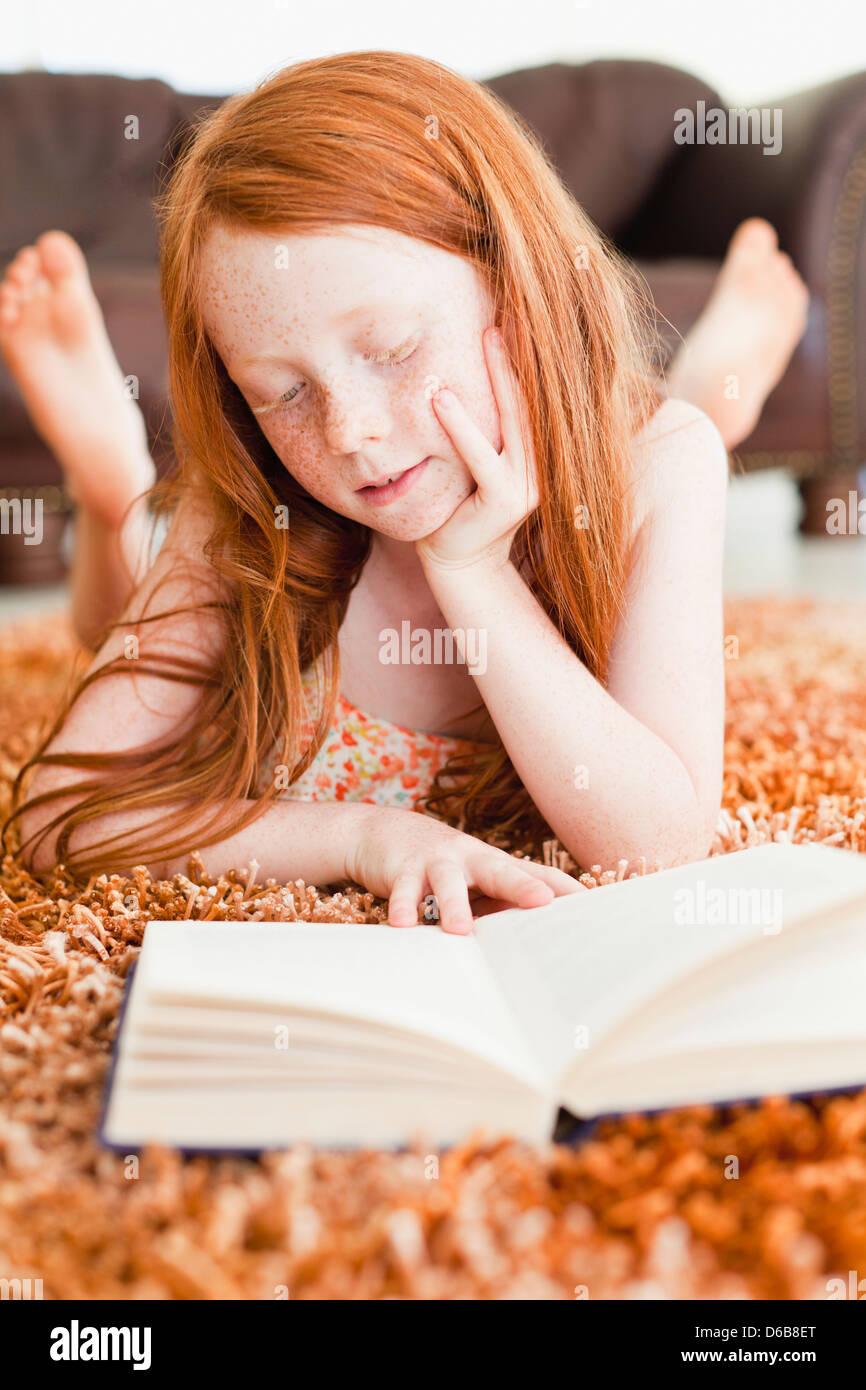 Mädchen lesen am Boden des Wohnzimmers Stockbild