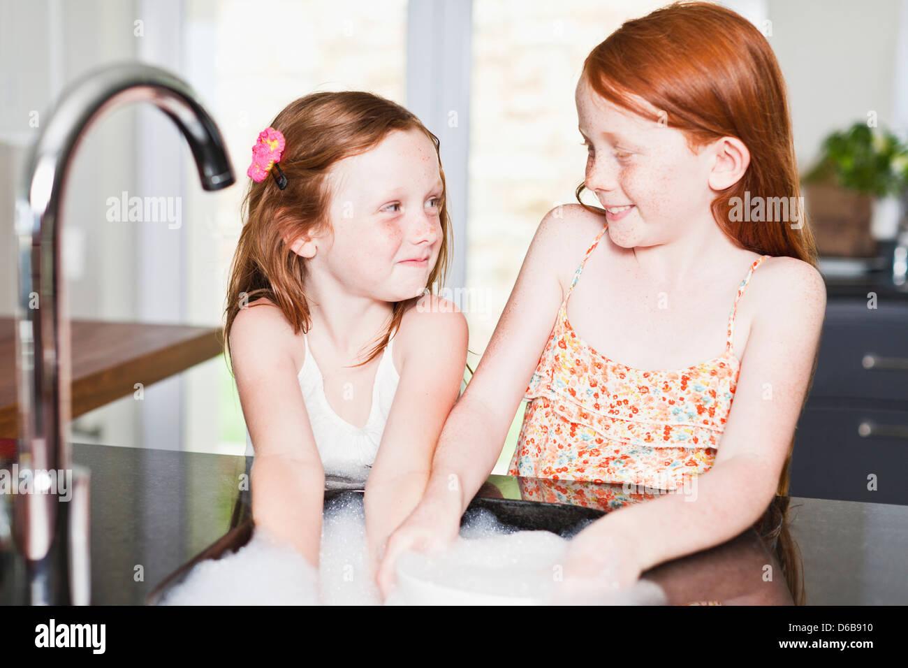 Lächelnde Mädchen Geschirr in der Spüle Stockbild