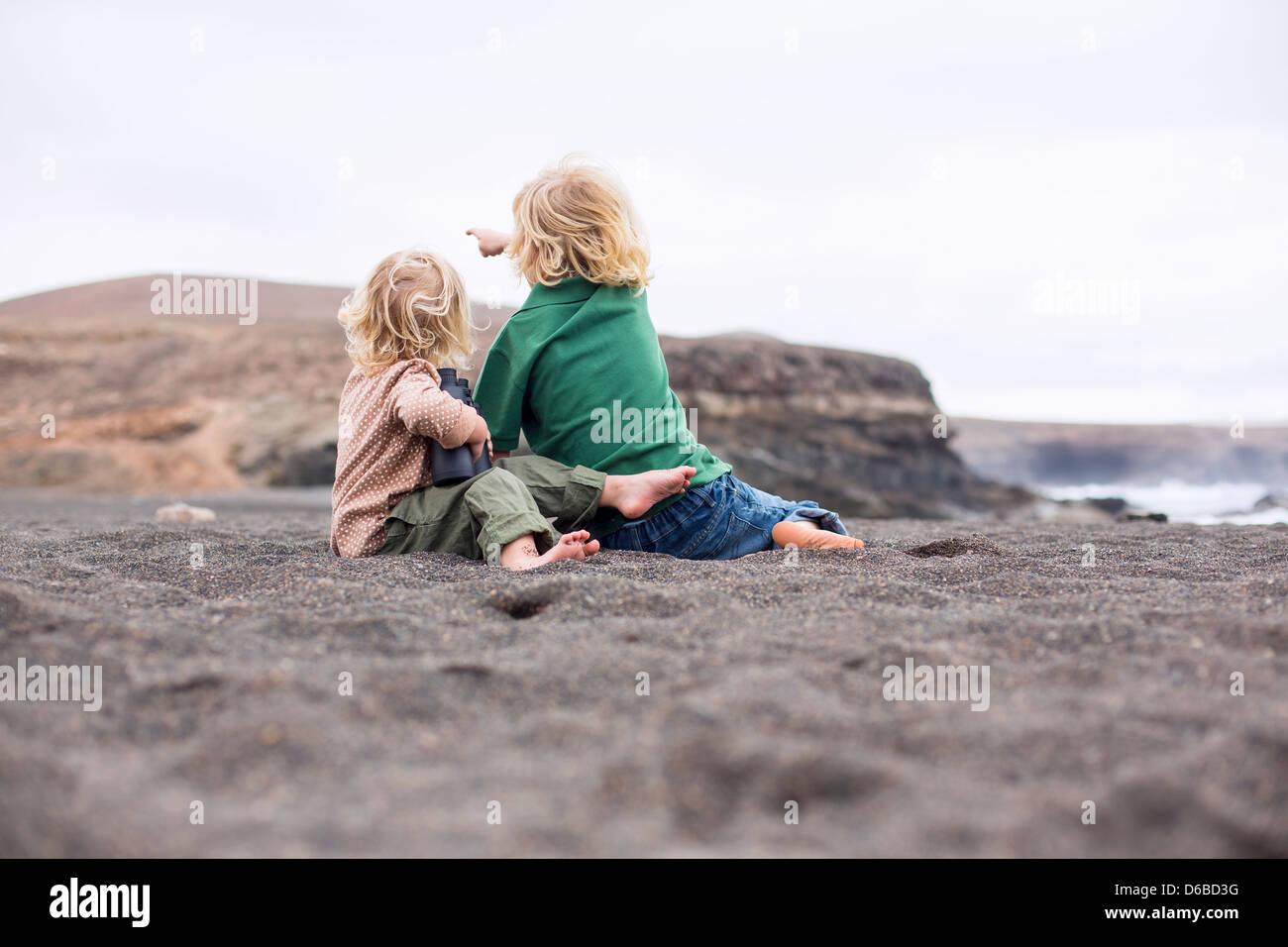 Kinder sitzen in Sand am Strand Stockbild
