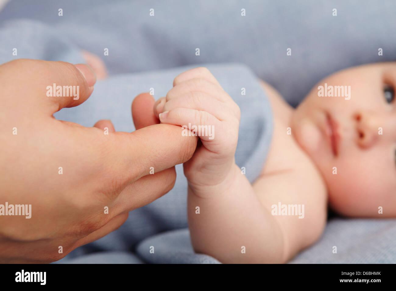 Baby Boy mit Müttern Finger im Bett Stockbild
