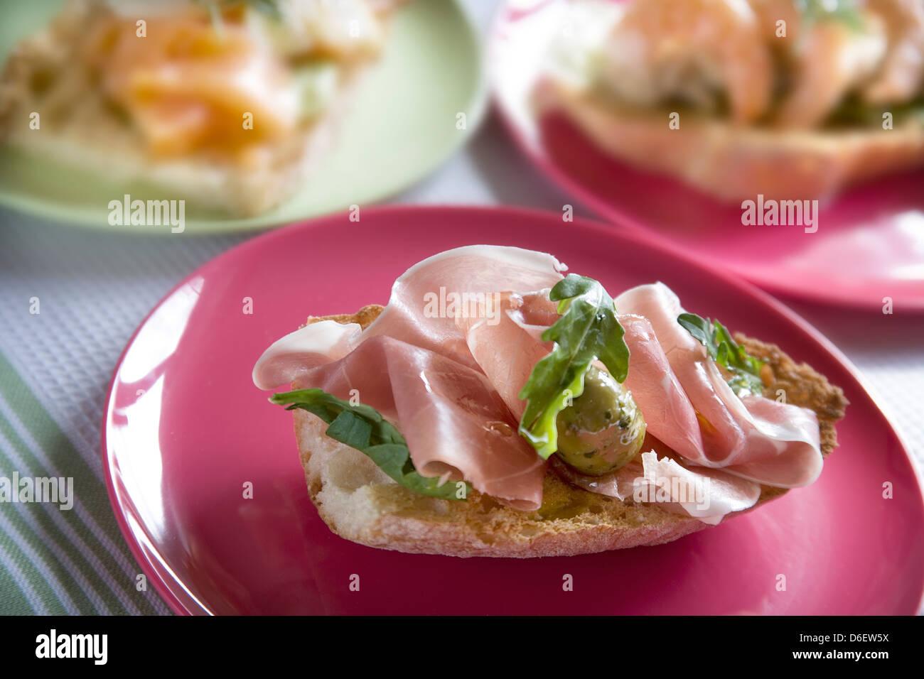 Rustikales Brot getoastet und mit dünn geschnittenem Schinken, grünen Oliven und Rucola garniert Stockbild