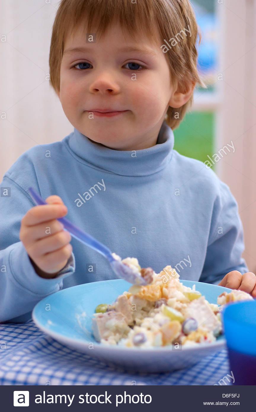 Kleiner Junge Essen ein fruchtiger Geflügelsalat Stockbild