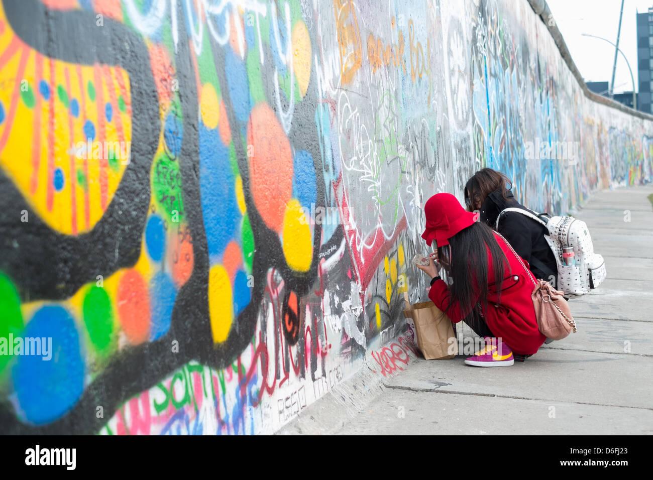Asiatische Touristen schreiben an die Berliner Mauer in der Eastside Gallery Stockbild