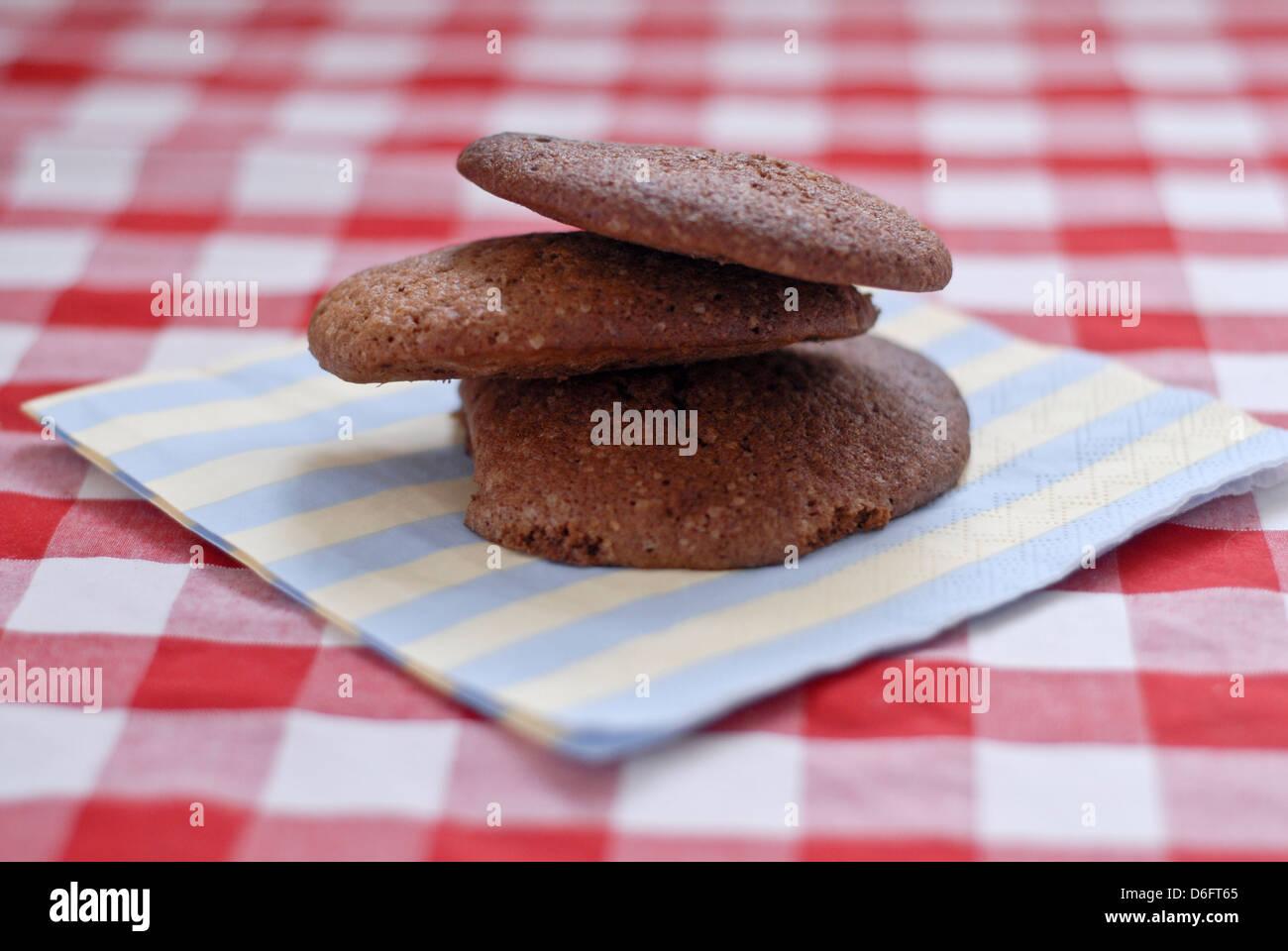 Schokoladen-Plätzchen auf einer aufgegebenen Tischdecke Stockbild