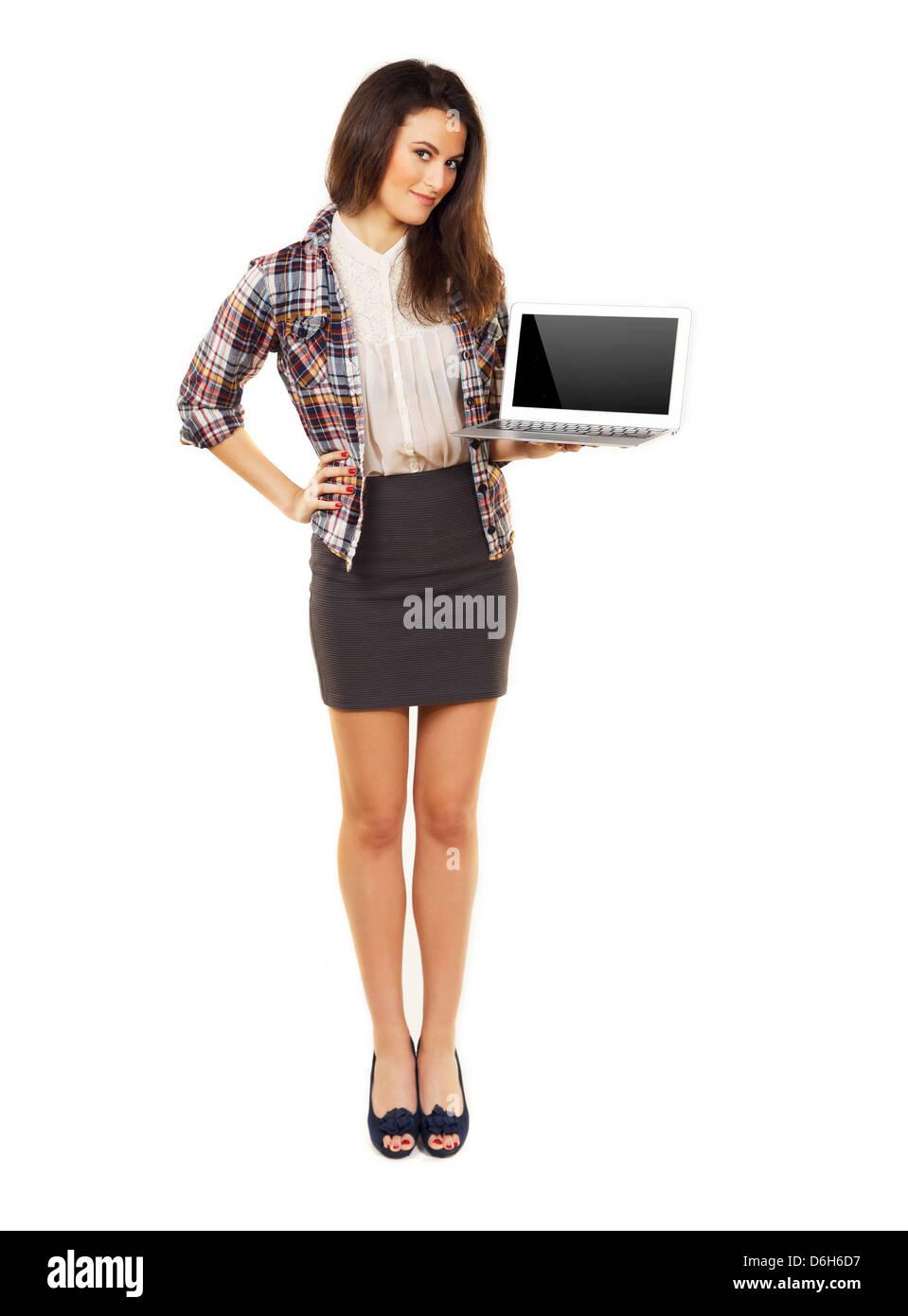 Voller Länge Frau in einem Studio zeigt Exemplar auf dem Laptop Bildschirm Stockbild