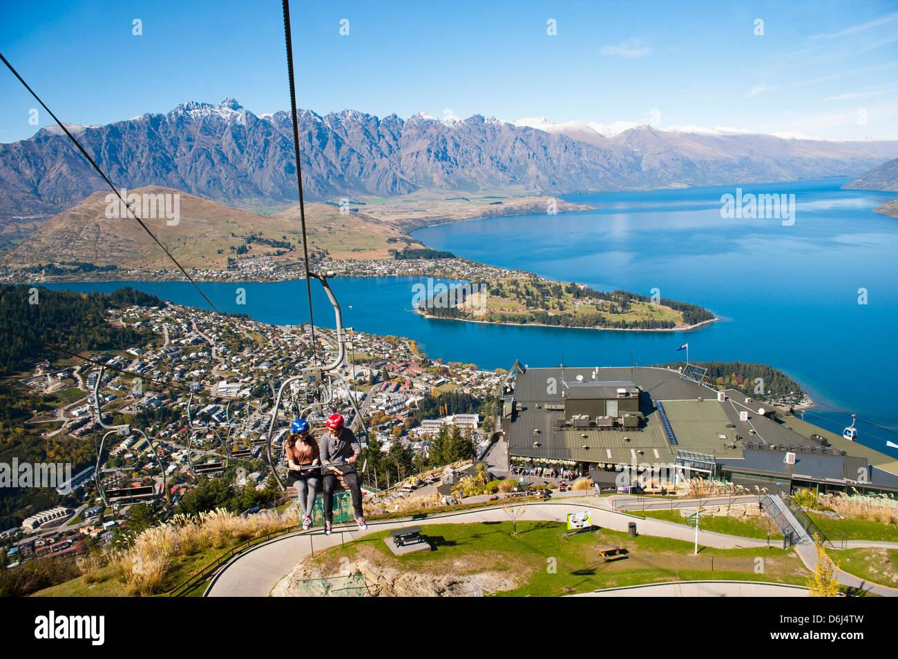 Zwei Touristen auf die Gondel auf der Rodel verfolgen über Queenstown, Otago, Südinsel, Neuseeland, Pazifik Stockbild
