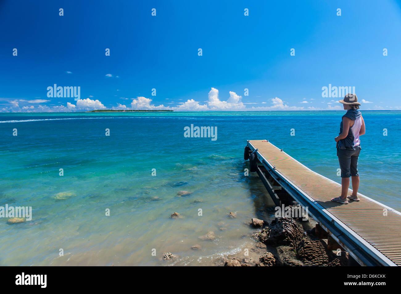Touristen stehen auf einem kleinen Pier mit Cocos Island in der Ferne, Guam, US-Territorium, Central Pacific, Pazifik Stockbild