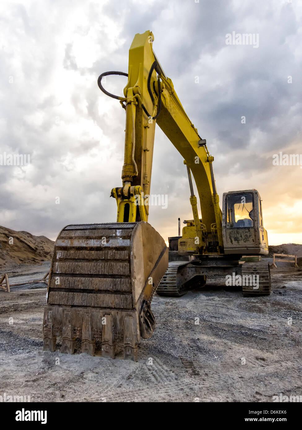 Gelbe Bagger Lader Maschine auf Baustelle über ein bewölkter Himmel Stockbild