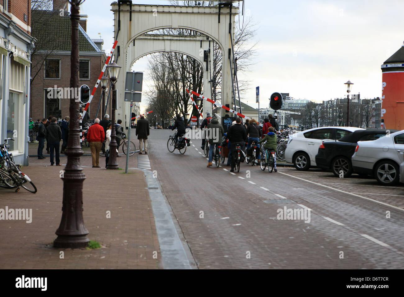 Licht Tour Amsterdam : Radfahrer und fußgänger warten auf ein rotes licht und barriere