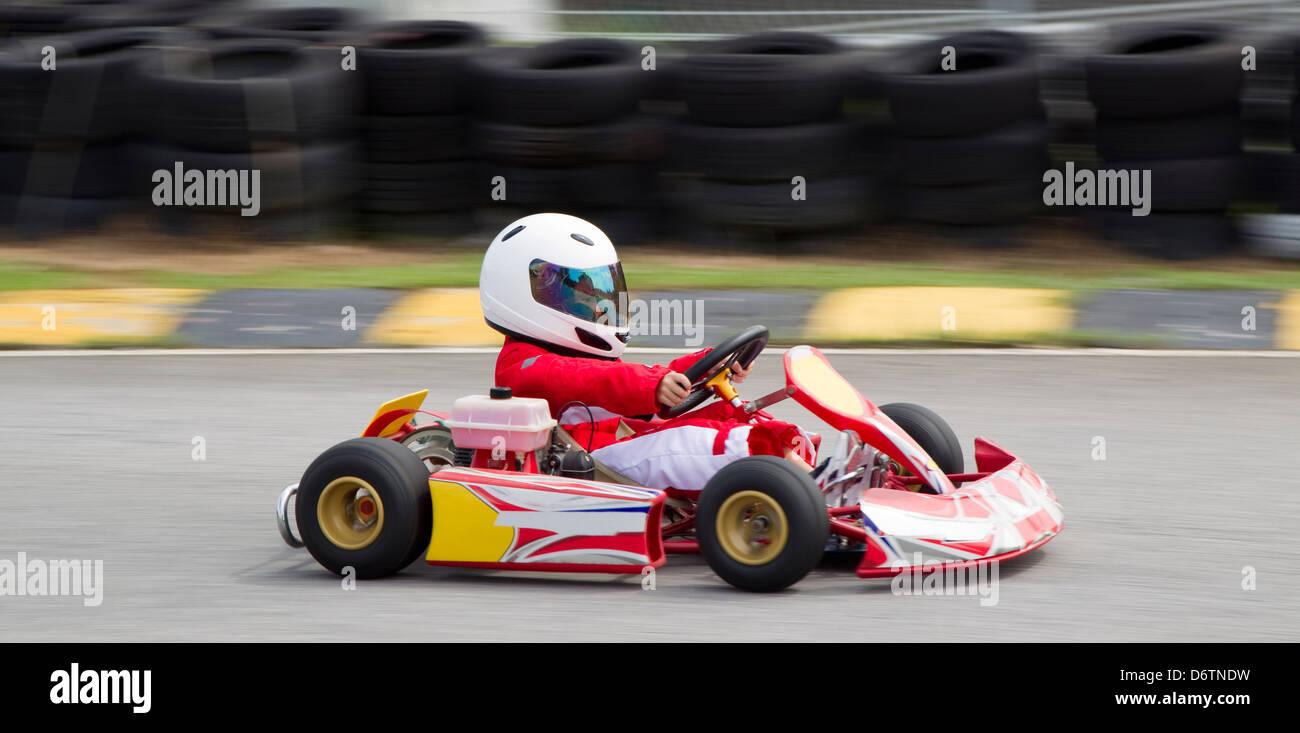 Junge asiatische Junge in einer roten und weißen Rasse Anzug und Helm in einem Go Kart Stockbild