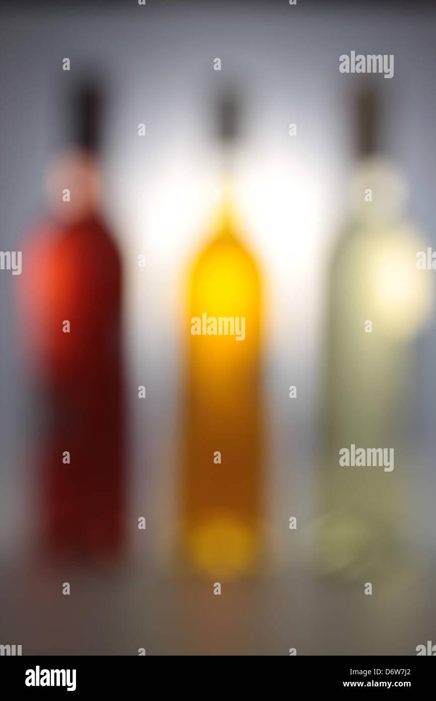 Drei Weinflaschen mit Hintergrundbeleuchtung und grauen Hintergrund Stockbild