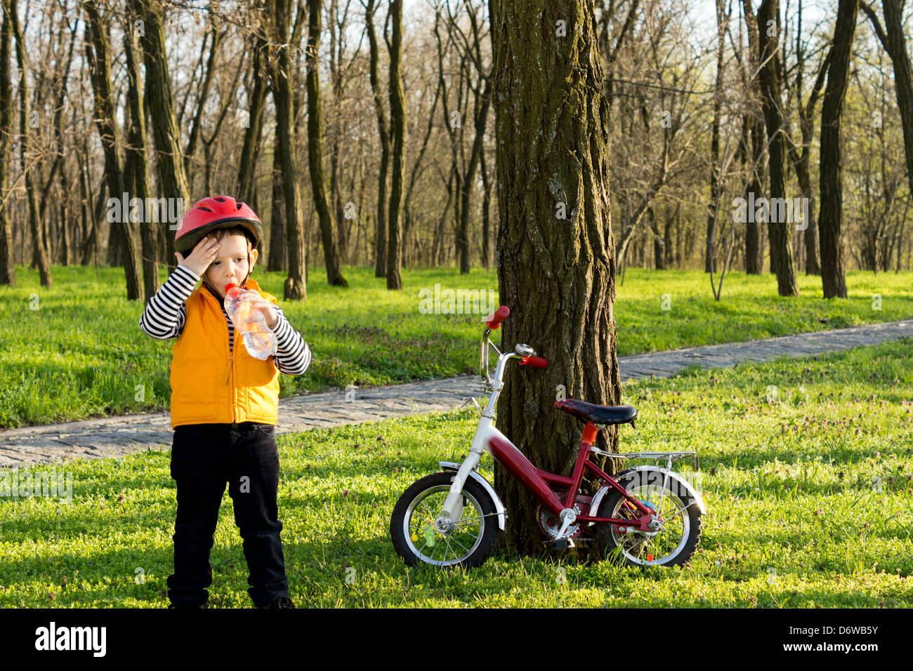 niedliche kleine junge radfahren mit seinem fahrrad im. Black Bedroom Furniture Sets. Home Design Ideas