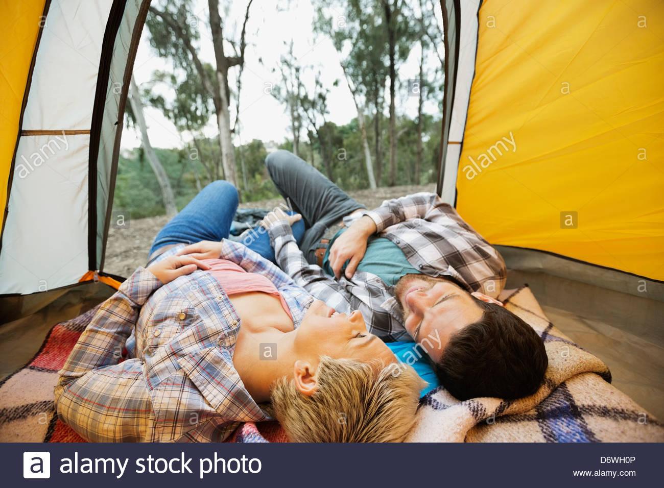 Glückliches Paar zusammen im Zelt liegend Stockbild
