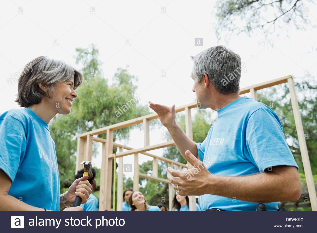 Reifer Mann und Frau im Gespräch, während Freiwillige Holzrahmen im Hintergrund bauen Stockbild