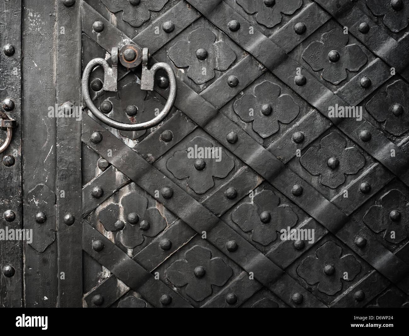 Alte schwarze Tür mit Nieten und Blumenmuster Stockbild