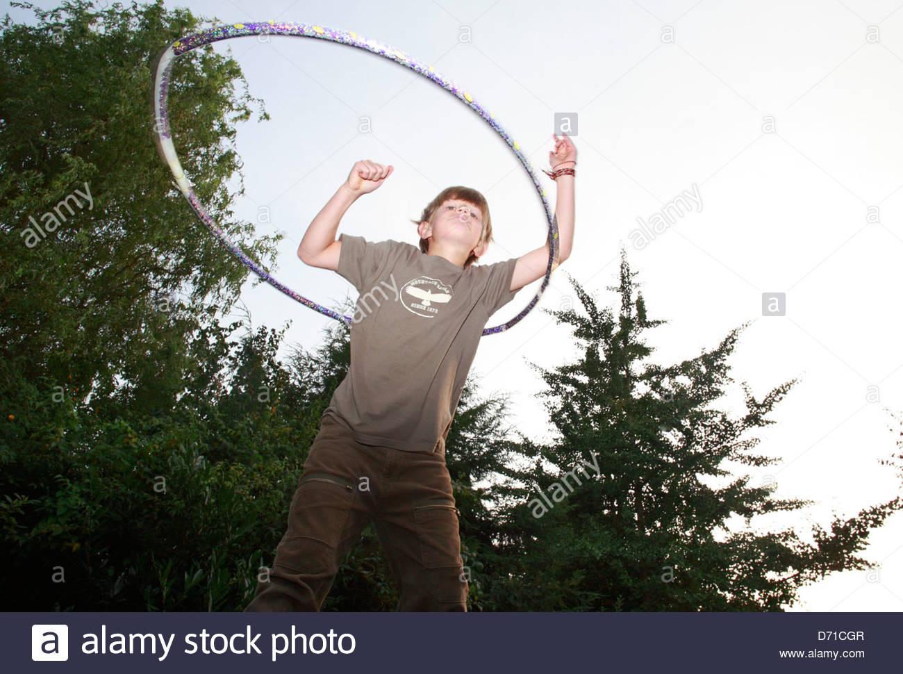 Niedrigen Winkel Blick auf ein Junge spielt mit einem Hula-Hoop Stockbild
