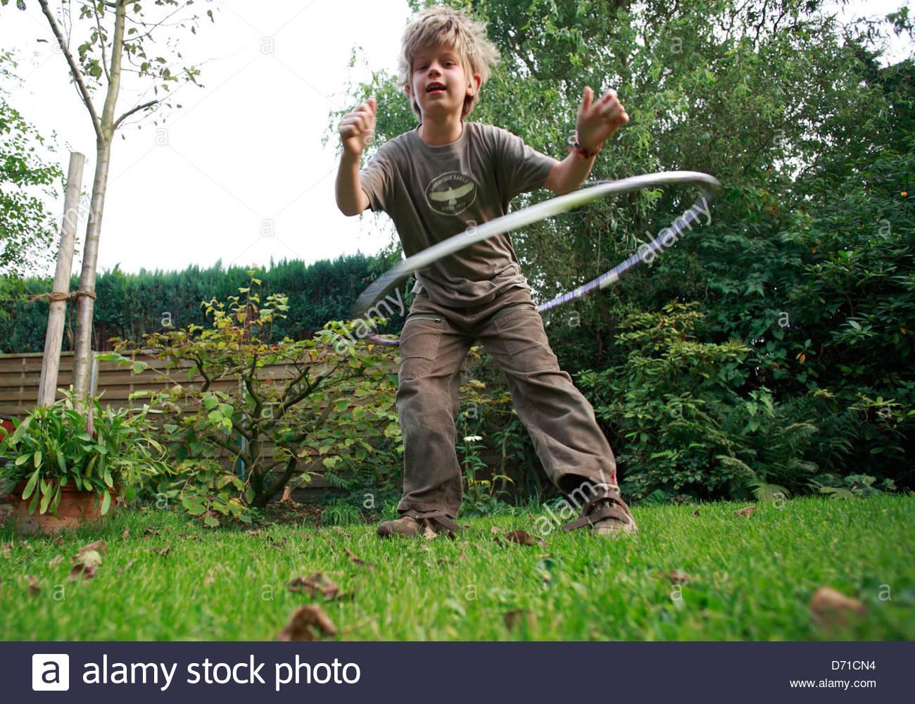 Junge spielt mit einem Hula-Hoop in einem Garten Stockbild