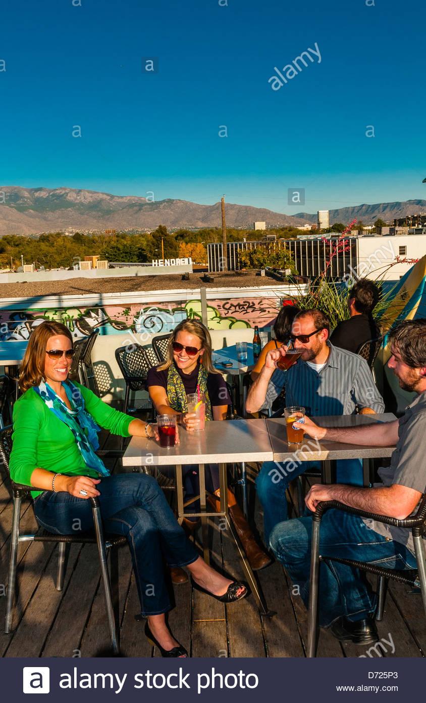 """Freunde, die Getränke auf der Dachterrasse des """"Baileys am Strand', Nob Hill, Albuquerque, New Mexico, Stockbild"""