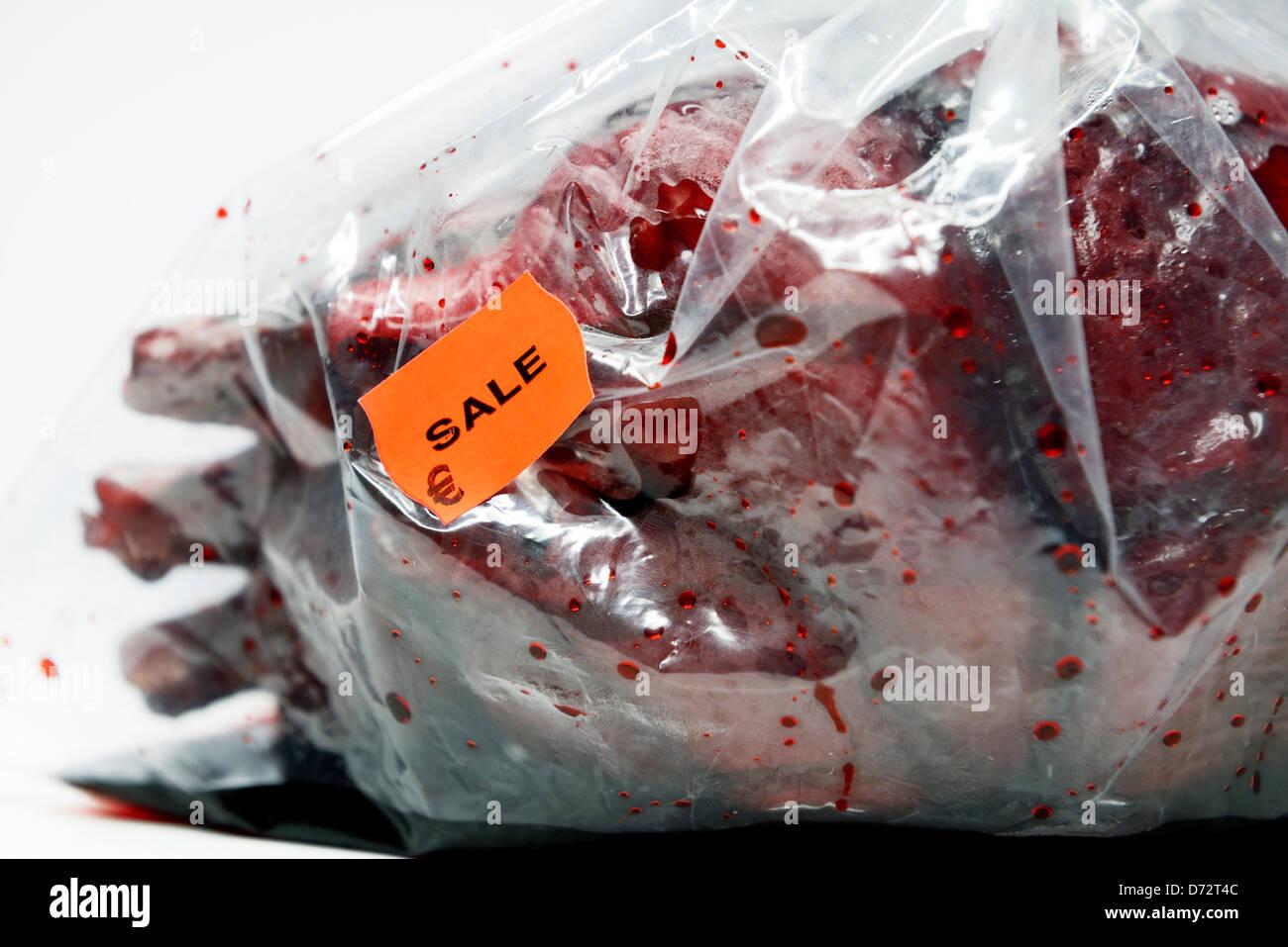 Herzen in einer Plastiktüte mit Preis-Label, symbolische Foto-Organ-Spende-Skandal Stockbild