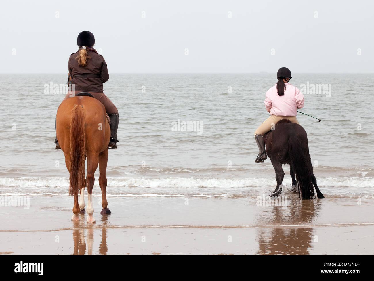 Zwei junge Frauen auf Pferden reiten am Strand von den Gewässern Rand Holkham Beach-Norfolk UK Stockbild
