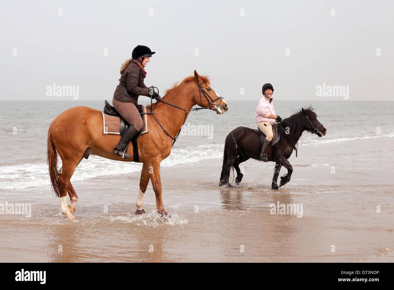 Zwei junge Frauen, die Reitpferde auf Holkham Beach, North Norfolk Küste, East Anglia, England Stockbild