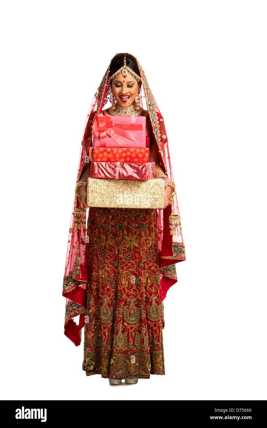 Lächelnde indische Braut in traditionellen Brautkleid hält Geschenke ...